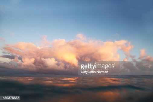Clouds over sea at sunrise : Stock Photo