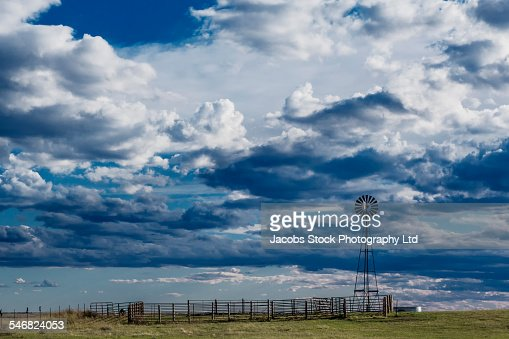 Clouds over windmill on ranch in rural landscape