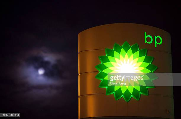 Clouds partially cover the moon beyond an illuminated BP logo as it sits on a sign outside a gas station operated by BP Plc in Guildford UK on Monday...