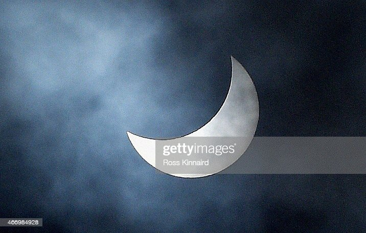 Clouds pass across the sun which is pictured during a partial solar eclipse over the Madeira Islands The moon was scheduled to cover approximately...