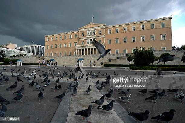 Clouds pass over the Greek parliament in Athens on September 17 2012 Greece's government continue talks as it struggles to finalise a 116billioneuro...