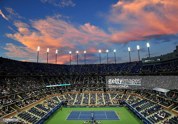 Clouds reflect light from the setting sun over Arthur Ashe Stadium as Victoria Azarenka of Belarus plays Daniela Hantuchova of Slovakia during their...