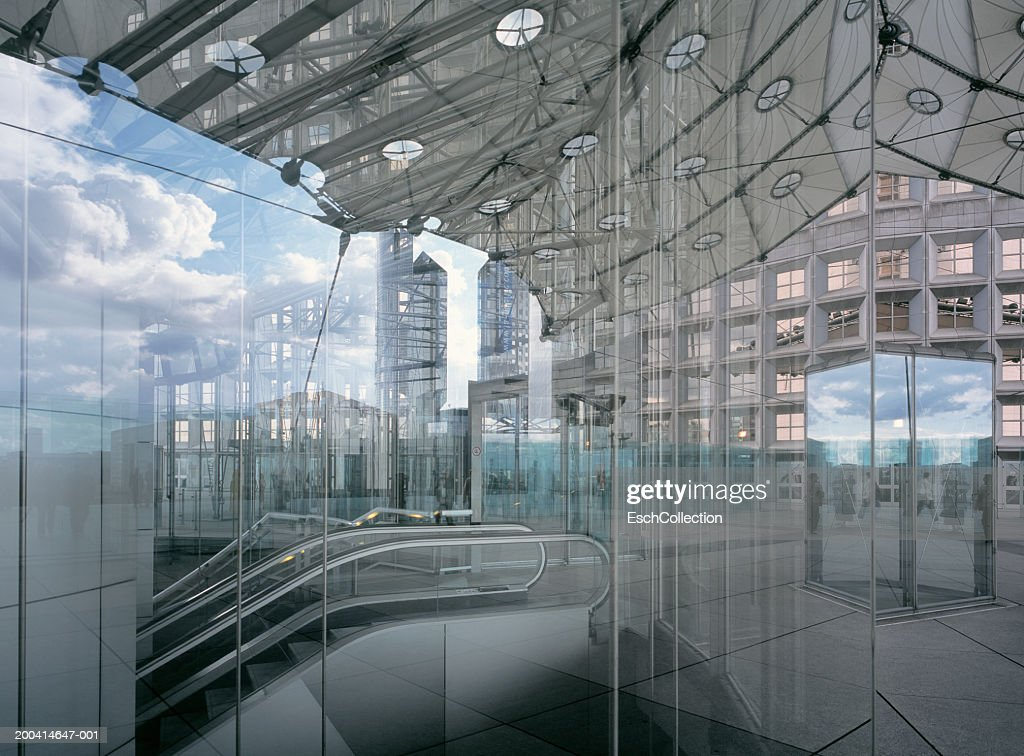 Clouds reflected in glass building with escalator : Stock Photo