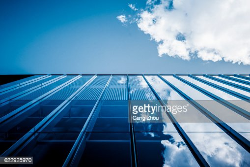 Clouds reflected in windows of modern office building : Stock Photo