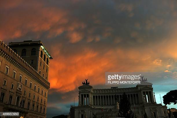 Clouds turn orange during a storm at sunset on December 4 2014 at Piazza Venezia in Rome AFP PHOTO / FILIPPO MONTEFORTE