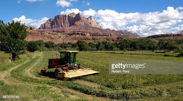 cloudscape and summer pastures with equipment cutting hay Rockville Utah