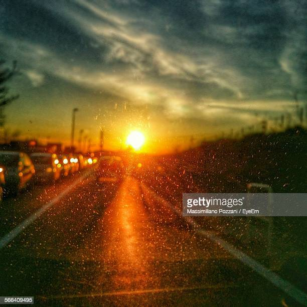 Cloudy Sky And Shining Sun Over Parked Cars On Road Seen From Car Windshield