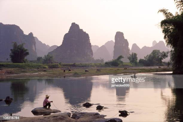 A cloudy sunset of Li River with man with pet