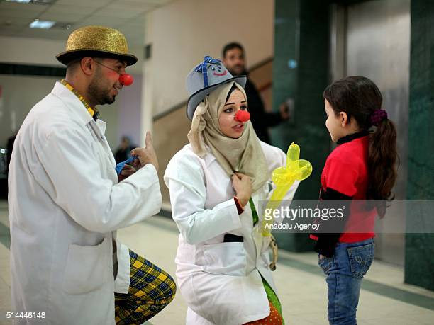 Clown doctors chat with a patient child girl during a visit at Abdel Aziz AlRantisi hospital in Gaza City Gaza March 9 2016