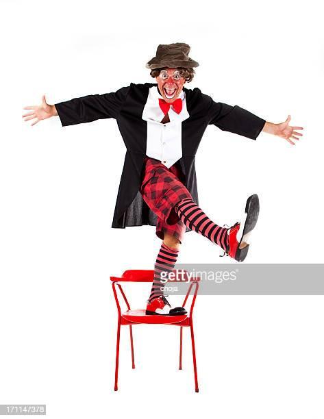 Clown übst tricks auf einem Stuhl