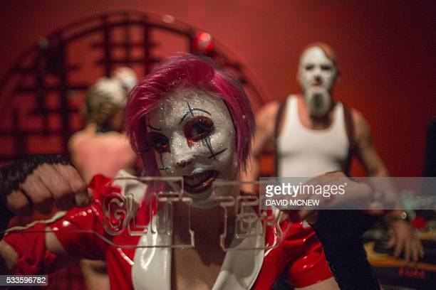 Clown dominatrix Dutchess holds a paddle she broke spanking voluntary submissive Hello Kitty while dominating her with Matlock at a dungeon party...