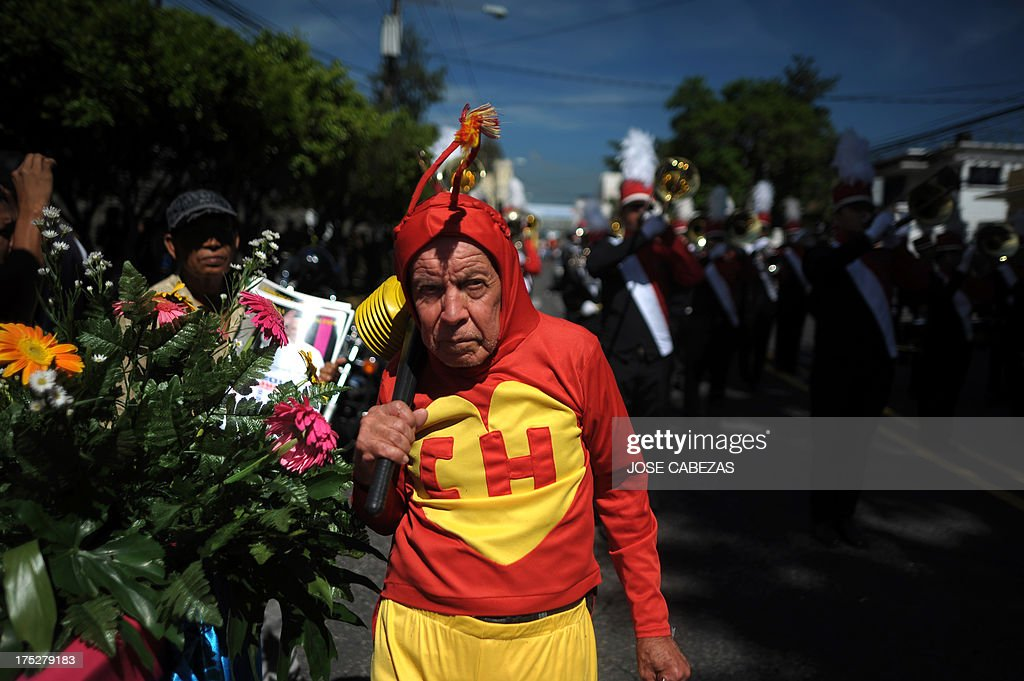 A clown dressed as the Mexican TV character El Chapulin Colorado participates in the parade of El Correo, the opening of the celebration of the El Divino Salvador del Mundo, patron saint of the city of San Salvador, El Salvador, on August 1, 2013. AFP PHOTO / Jose CABEZAS