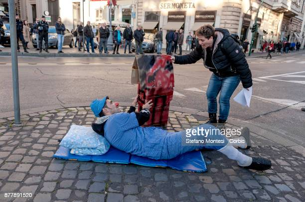 A clown dressed demonstrator acts as a homeless street sleeper during a demonstration by the Movements for the right to housing against the Five star...