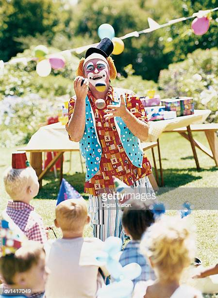 A Clown Entertains Children at a Party with Juggling