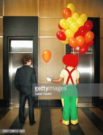 Clown handing businessman balloon in lobby, rear view