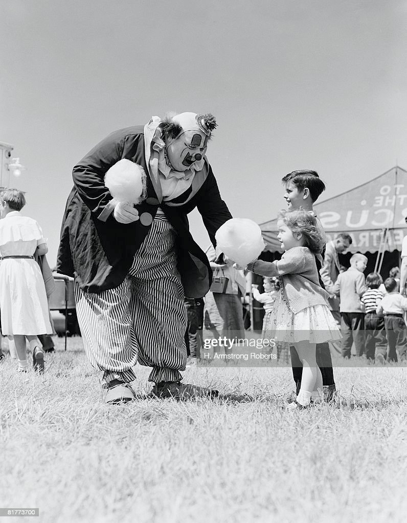 Clown handing cotton candy to children outside circus tent. : Stockfoto