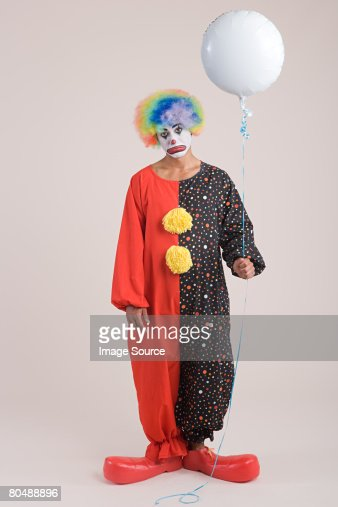 A clown holding a balloon