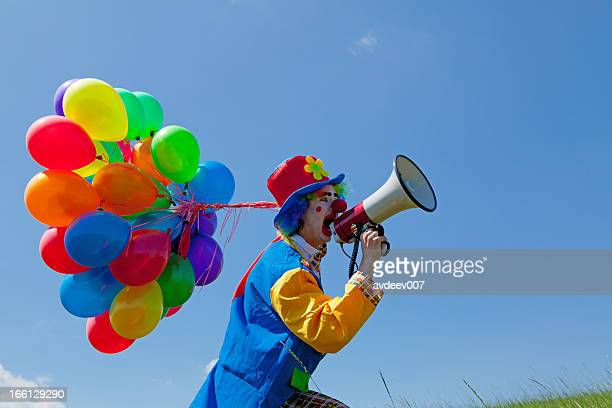 Clown holding balloons and crying  to megaphone