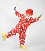 Clown holding horn, standing on one leg, portrait