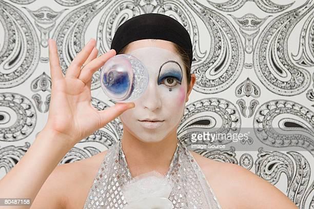 Payaso mirando a través de una bola de cristal