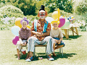 Clown Sitting on a Chair With Two Young Boys in a Garden