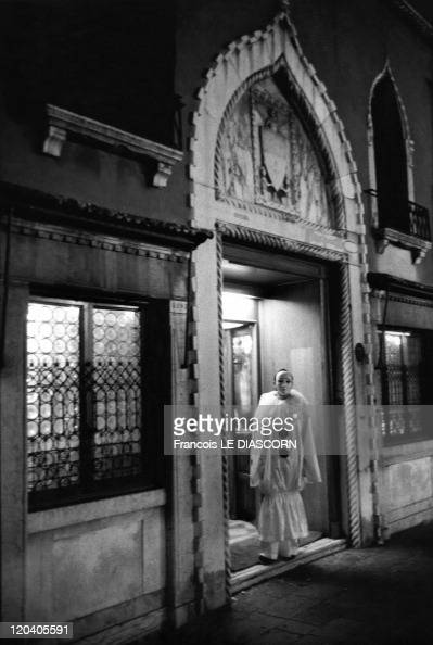 Clown standing in a Renaissance doorway in Venice Italy Clown standing in a Renaissance doorway at night looking out Venice Carnival