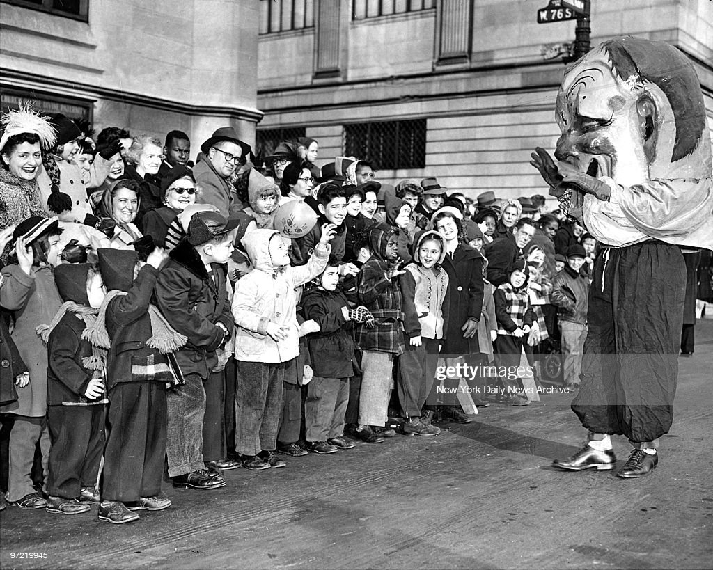 A clown whose 'head' is in danger of blowing away becomes big favorite with kiddies jamming street along Central Park West at Macy's Thanksgiving Day parade.