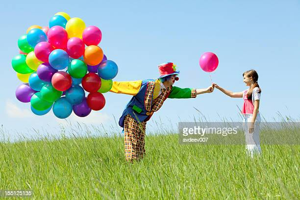 Clown with balloon bouquet giving one to a girl in a field