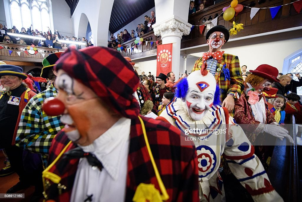 Clowns call for order at the start of the 70th annual 'Clowns International' church service at the Holy Trinity church in Dalston in east London, England on February 7, 2016. The service takes place to celebrate the father of modern clowning, Joseph Grimaldi, who died in 1837. / AFP / LEON NEAL