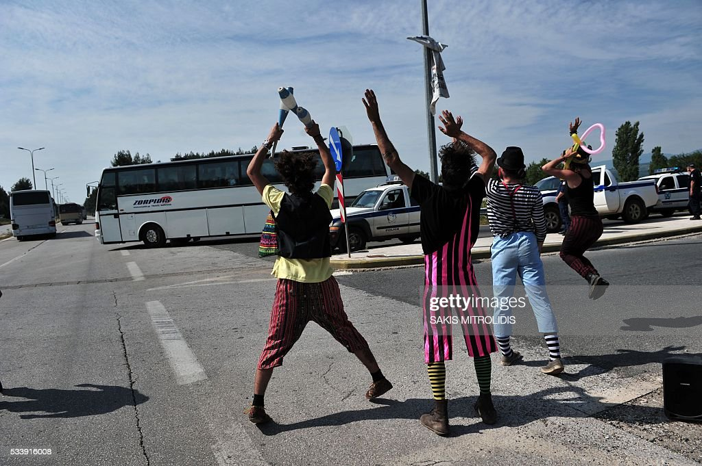 Clowns from a solidarity group wave to migrants onboard a bus, as they are evacuated from the makeshift camp at the Greek-Macedonian border, near the Greek village of Idomeni, on May 24, 2016. Hundreds of Greek police on May 24 began clearing the overcrowded Idomeni camp, a migrant flashpoint on the Macedonia border where thousands have been living in squalid conditions for more than three months. Over 800 people were put on buses to newly-opened camps in the vicinity of Greece's second city Thessaloniki, about 80 kilometres (50 miles) to the south in an operation that began shortly after sunrise, police said. MITROLIDIS