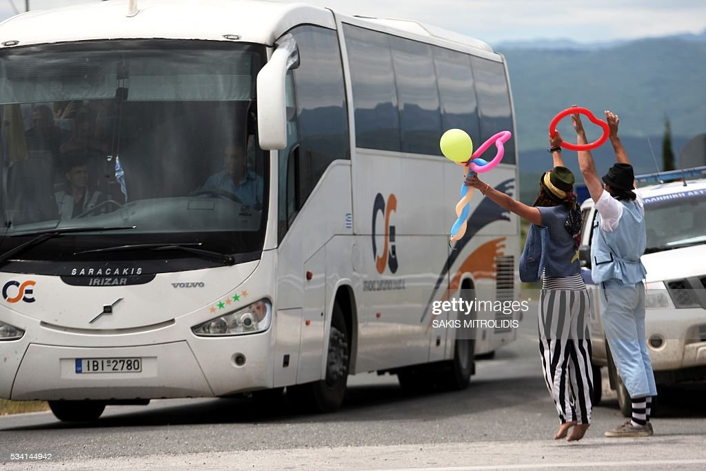 Clowns from a solidarity group wave to migrants onboard a bus, as they are evacuated from the makeshift camp at the Greek-Macedonian border, near the Greek village of Idomeni on May 25, 2016. In an operation which began shortly after sunrise on May 24, hundreds of Greek police began evacuating the sprawling camp which is currently home to 8,400 refugees and migrants, among them many families with children, an AFP correspondent said. At its height, there were more than 12,000 people crammed into the site, many of them fleeing war, persecution and poverty in the Middle East and Asia, with the camp exploding in size since Balkan states began closing their borders in mid February in a bid to stem the human tide seeking passage to northern Europe. / AFP / SAKIS