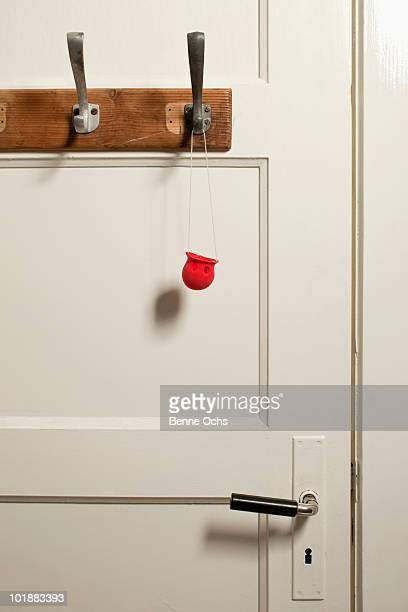 A clown's nose hanging on a coat hook