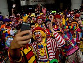 Clowns pose for a selfie after a parade during the Clown Festival in Kuala Lumpur on August 17 2014 Around 80 clowns from all over Malaysia took part...