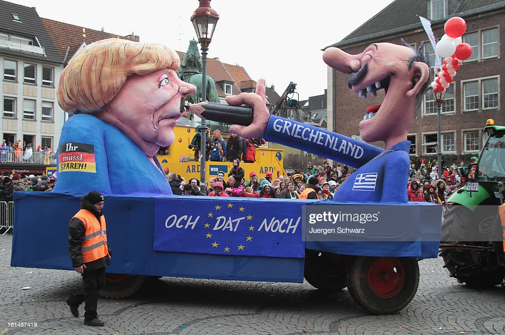 Clowns stand in front of a float featuring a Greek man painting a moustache under German Chancellor Angela Merkel's during the carnival parade on February 11, 2013 in Dusseldorf, Germany. Rose Monday is the highpoint of the annual carnival season in the region between Mainz, Cologne and Dusseldorf, where carnival has been an annual tradition since 1823 and celebrates free-spirited merrymaking before the beginning of Lent.