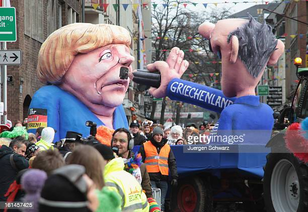Clowns stand in front of a float featuring a Greek man painting a moustache under German Chancellor Angela Merkel's during the carnival parade on...