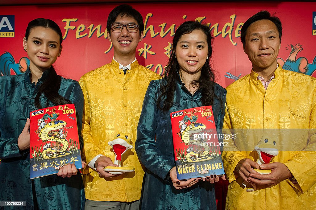 CLSAÕs research analysts Oliver Lam (C-L) and Francis Cheung (R), along with research associate Mariana Kou (2nd R) and institutional salesperson Emily Lam (L) display the CLSA Feng Shui Index 2013, an annual tongue-in-cheek prediction on financial markets and world affairs, during a press conference in Hong Kong on February 6, 2013. Astrologers say the snake that will be roaming this year is identified with the element of water -- which symbolises fear -- that sits on top of the fire element, which represents joy and optimism. AFP PHOTO / Philippe Lopez