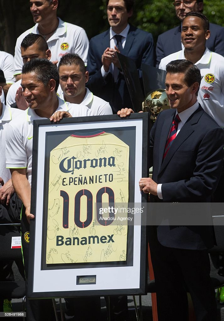 Club America 's coach, Ignacio Ambriz (L) and President of Mexico, Enrique Pena Nieto are seen during a visit of Club America to the Los Pinos Presidential Palace, after wining the CONCACAF Champions League Final in Mexico City, Mexico on April 29, 2016.