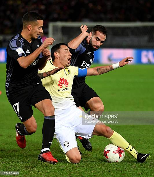 Club America's forward Oribe Peralta is tackled by Real Madrid's midfielder Lucas Vazquez and defender Daniel Carvajal during the Club World Cup...