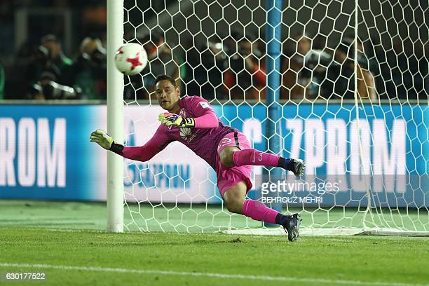 CORRECTION Club America's goalkeeper Moises Munoz watches the ball as Atletico Nacional's forward Miguel Borja scores the last penalty in the...