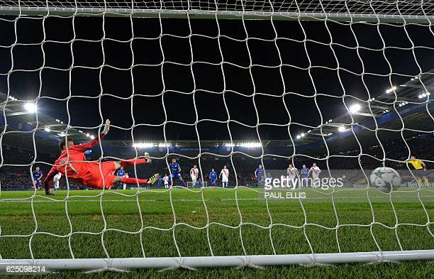 Club Brugge's French goalkeeper Ludovic Butelle dives as Leicester City's Algerian midfielder Riyad Mahrez scores his team's second goal from the...