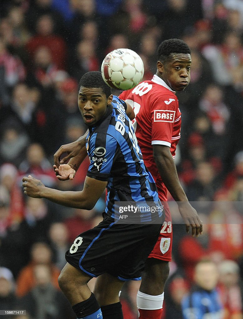 Club Brugge's Ryan Donk (L) and Standard de Liege's Michy Batshuayi fight for the ball during their Jupiler Pro League match in Liege on December 23, 2012, on day 21 of the Belgian football championship.