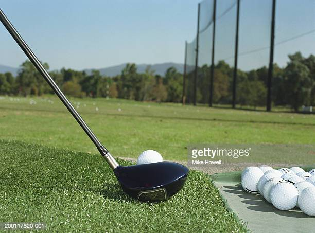 Club lined up with golf ball on driving range (ground view)