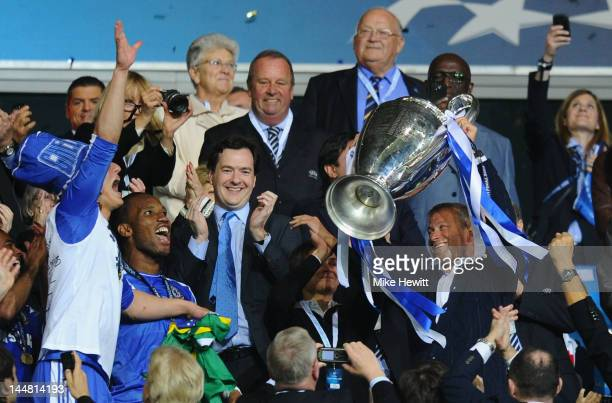 Club owner Roman Abramovich lifts the trophy in celebration while Chancellor of the Exchequer George Osborne applauds after their victory in the UEFA...