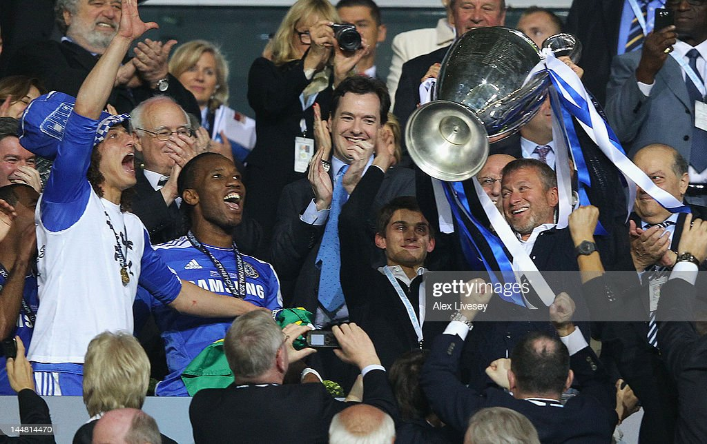 Club owner <a gi-track='captionPersonalityLinkClicked' href=/galleries/search?phrase=Roman+Abramovich&family=editorial&specificpeople=208953 ng-click='$event.stopPropagation()'>Roman Abramovich</a> (R) lifts the trophy in celebration while Chancellor of the Exchequer <a gi-track='captionPersonalityLinkClicked' href=/galleries/search?phrase=George+Osborne&family=editorial&specificpeople=5544226 ng-click='$event.stopPropagation()'>George Osborne</a> (C) applauds after their victory in the UEFA Champions League Final between FC Bayern Muenchen and Chelsea at the Fussball Arena München on May 19, 2012 in Munich, Germany.
