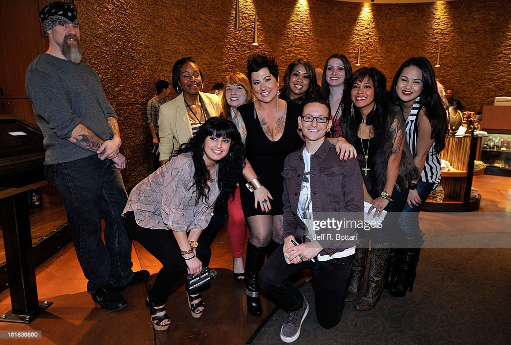 Club Tattoo co-owners and founders Thora Dowdell (5th L) and Linkin Park singer <a gi-track='captionPersonalityLinkClicked' href=/galleries/search?phrase=Chester+Bennington&family=editorial&specificpeople=213970 ng-click='$event.stopPropagation()'>Chester Bennington</a> (C) pose with fans during Linkin Park's autograph session at Club Tattoo inside the Miracle Mile Shops at Planet Hollywood Resort & Casino on February 16, 2013 in Las Vegas, Nevada.