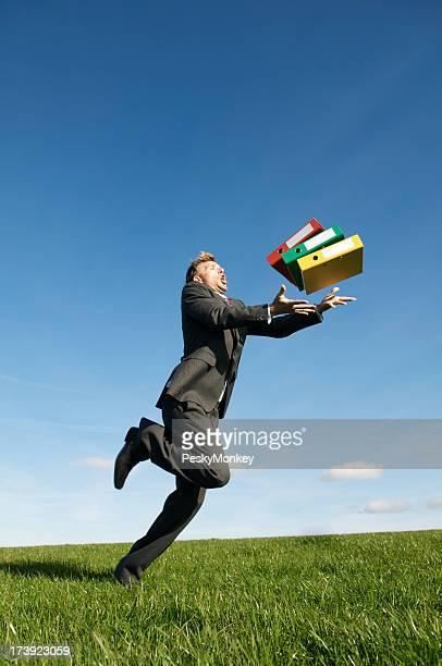 Groben Geschäftsmann Stolpern and Drop die Dateien im Meadow