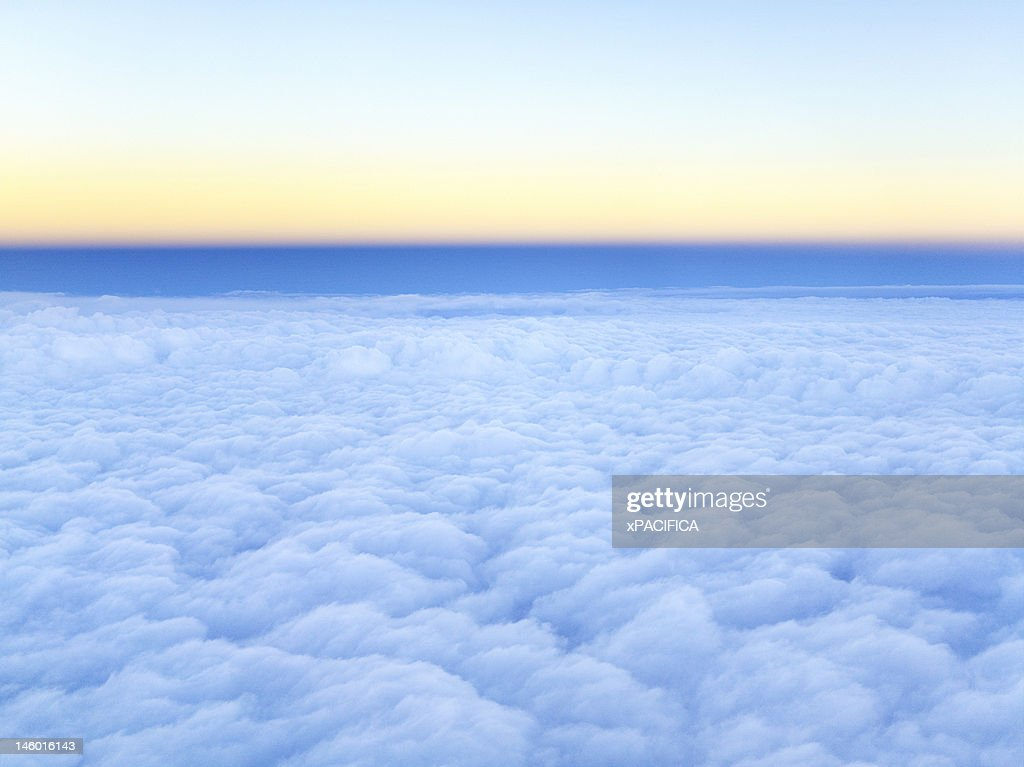 A cluster of clouds in the sky at dusk : Stock Photo