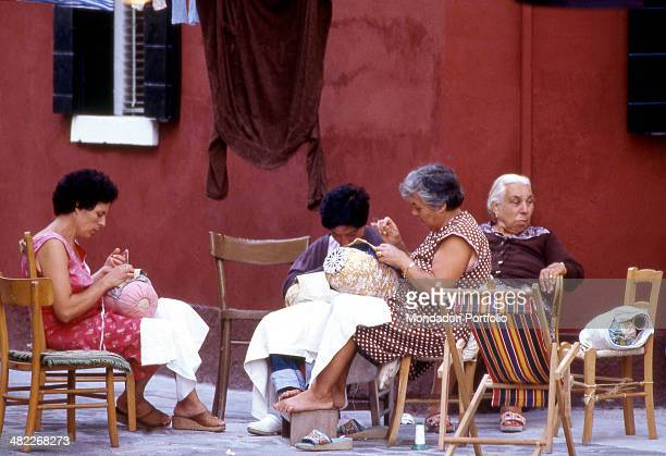 Cluster of women of Burano deep in working lace a typical centuriesold tradition handcraft activity of the island of the Venetian Lagoon sitting at a...