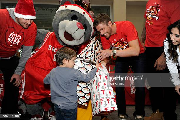 Clutch Mascot Chandler Parsons and Donatas Motiejunas of the Houston Rockets visit and pass out gifts to children on December 16 2013 at the Ronald...