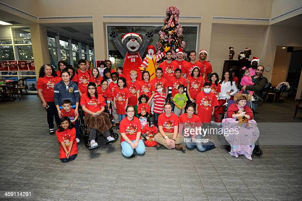 Clutch Mascot Chandler Parsons Omri Casspi Donatas Motiejunas and Greg Smith of the Houston Rockets pose for a photo after they visit and pass out...